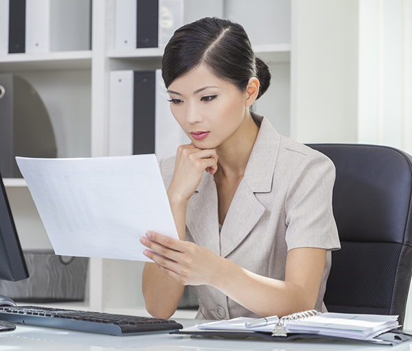 woman at her desk reading a documen t
